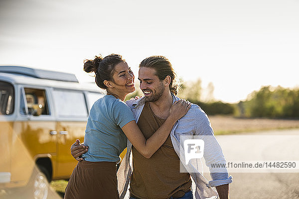 Happy couple doing a road trip with a camper  embracing on the road