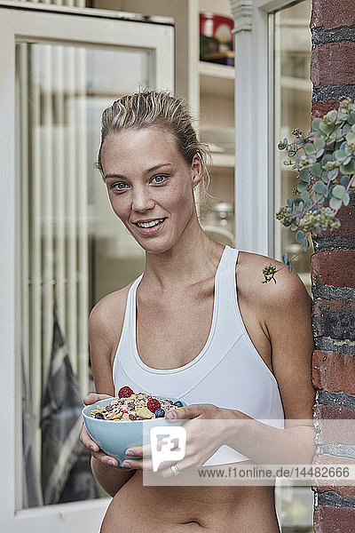 Portrait of smiling sporty young woman with muesli bowl at house entrance