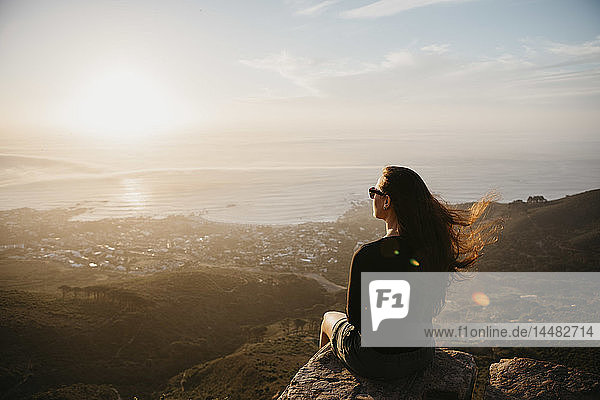 South Africa  Cape Town  Kloof Nek  woman sitting on rock at sunset