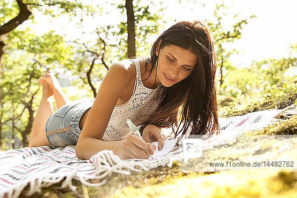 Junge Frau liegt auf einer Decke im Wald und schreibt einen Brief