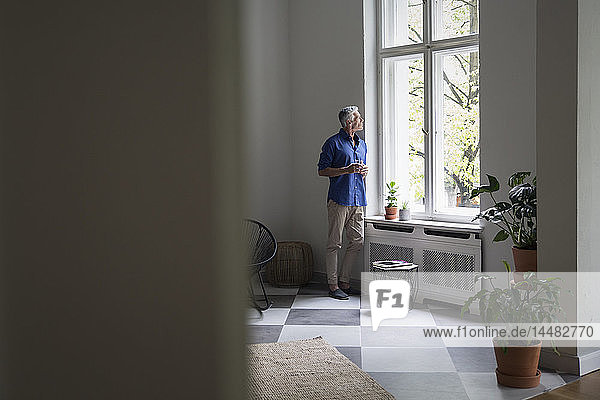 Mature man at home looking out of window