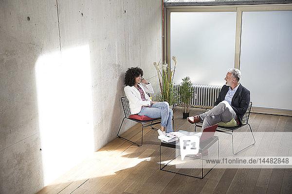 Geschäftsmann und Geschäftsfrau sitzen in einem Loft an einer Betonwand und unterhalten sich