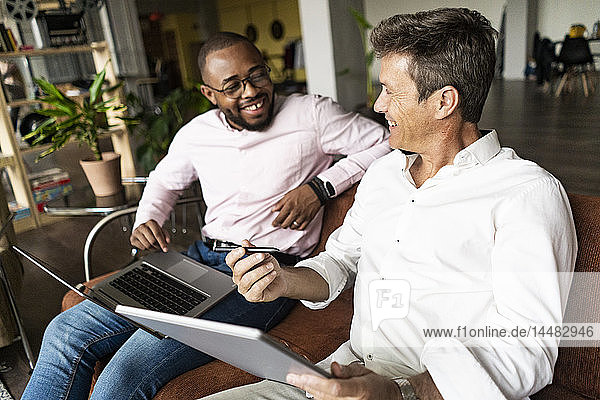 Two happy businessmen using laptop and tablet on sofa in loft office