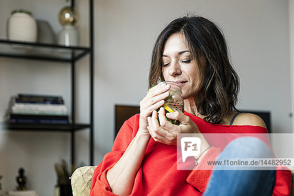 Mature woman relaxing at home  drinking lemon water