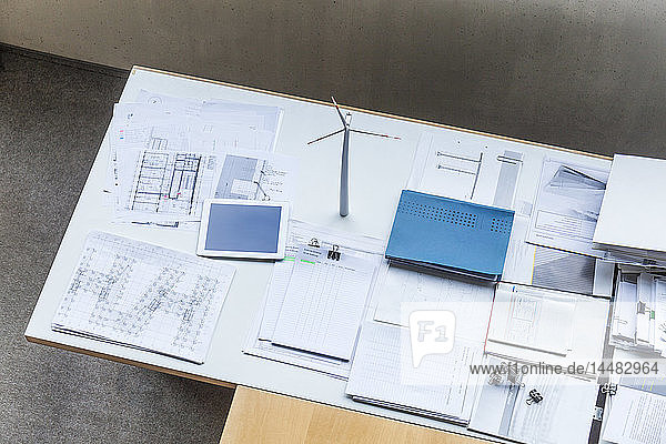 Wind turbine model,  construction plans and tablet on table in office