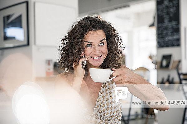 Reife Frau sitzt im Café  telefoniert  trinkt Kaffee