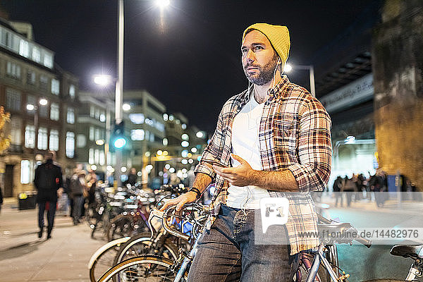 UK  London  man with bicycle and cell phone commuting at night in the city