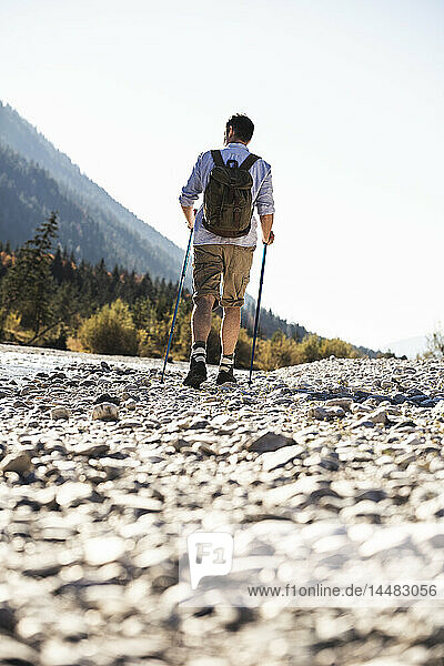 Austria,  Alps,  man on a hiking trip walking on pebbles along a brook