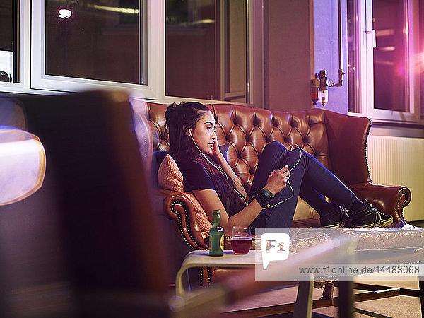 Junge Frau entspannt sich auf der Couch und hört Musik