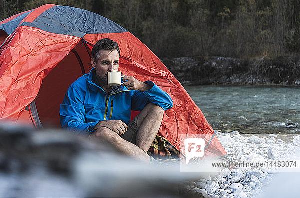 Erwachsener Mann zeltet am Flussufer  trinkt