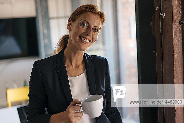 Porträt einer lächelnden Geschäftsfrau bei einer Kaffeepause im Büro