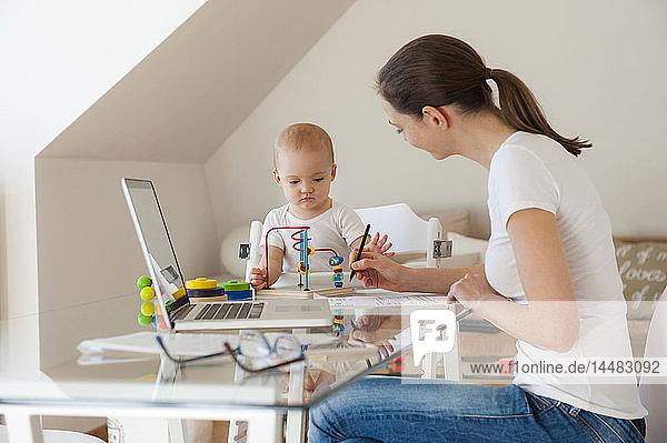 Mutter benutzt Laptop und kleine Tochter spielt zu Hause am Tisch