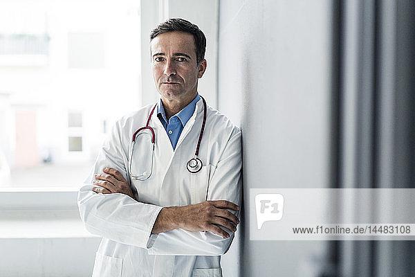 Porträt eines seriösen Arztes,  der gegen eine Wand lehnt