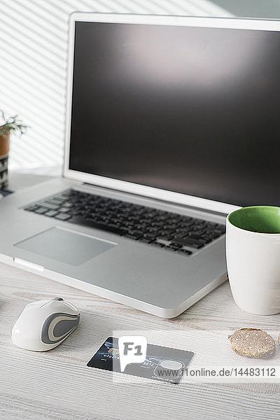 Büroschreibtisch mit Computermaus  Kreditkarte  Kaffeetasse und Keksen
