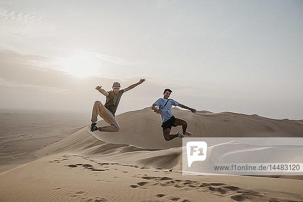 Namibia  Namib  zwei Freunde springen auf einer Wüstendüne in die Luft