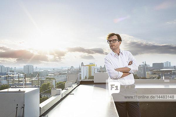 Deutschland  Berlin  Geschäftsmann steht abends auf der Dachterrasse und schaut in die Ferne