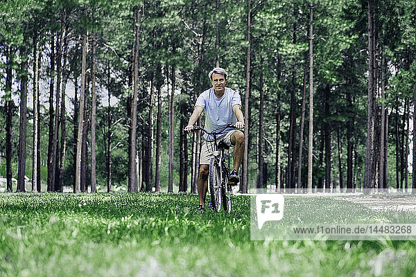Mature man sitting on bicycle in forest