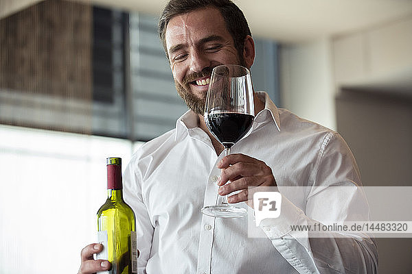 Mid adult man holding wine bottle and glass