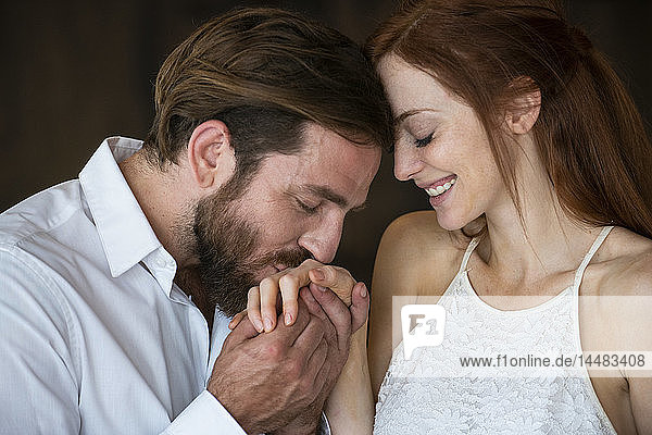 Close-up of man kissing his girlfriend's hand