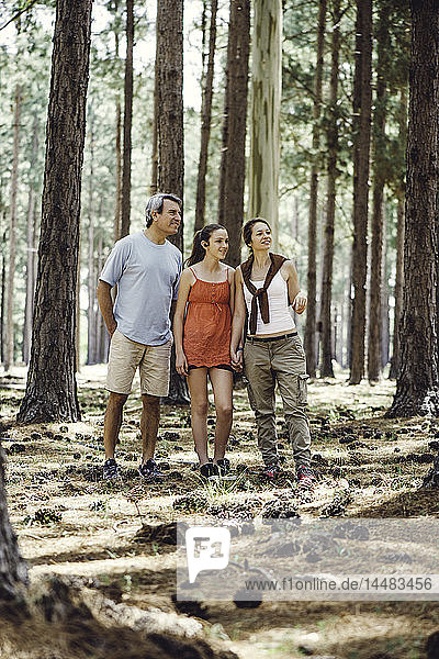 Family standing in forest