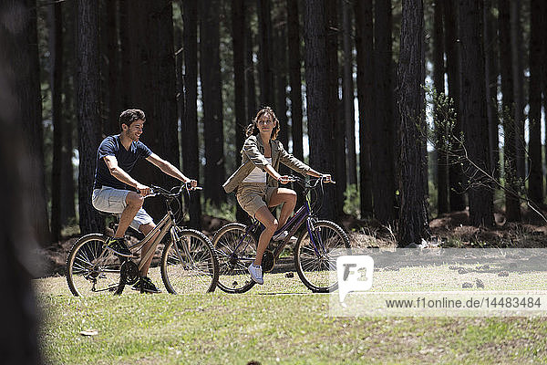 Young couple cycling on dirt track in forest