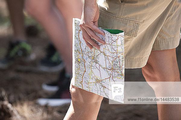 Woman's hand holding route map in forest