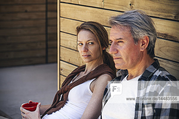 Couple sitting in front of log cabin