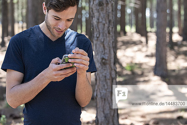 Young man using phone in forest