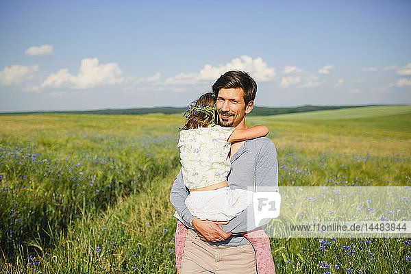Portrait father holding daughter in sunny  idyllic rural field with wildflowers