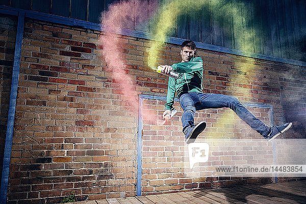 Portrait male modern dancer performing with spray paint against brick wall