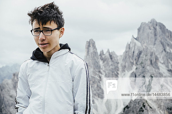 Teenage boy standing at rugged mountain peaks  Drei Zinnen Nature Park  South Tyrol  Italy