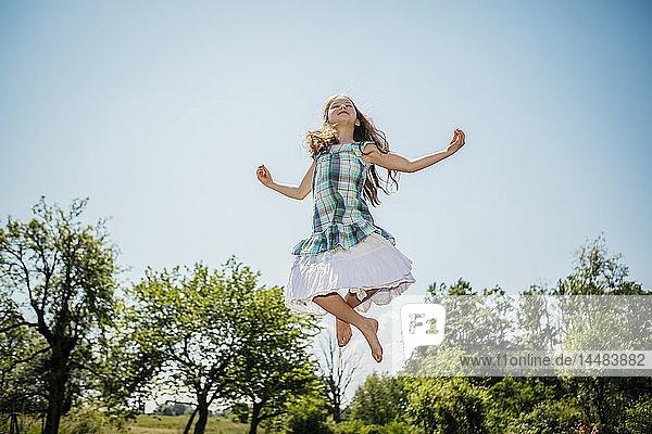 Carefree girl in dress jumping for joy in sunny backyard