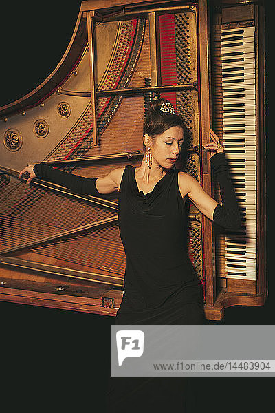 Elegant  well-dressed woman laying on piano