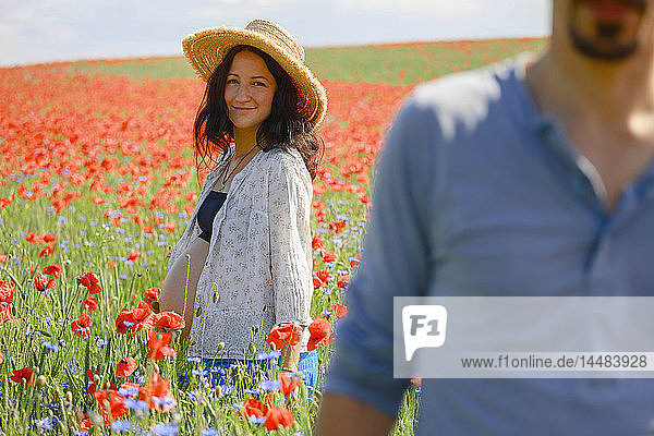 Portrait smiling pregnant woman standing in sunny  rural red poppy field