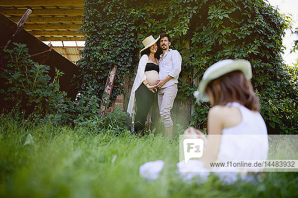 Pregnant couple watching daughter sitting in grass