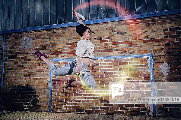 Female modern dancer performing with spray paint cans