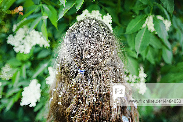 Girl with flowers in hair standing at flowering bush
