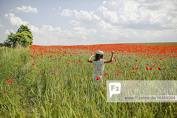 Girl running in sunny  idyllic rural red poppy field