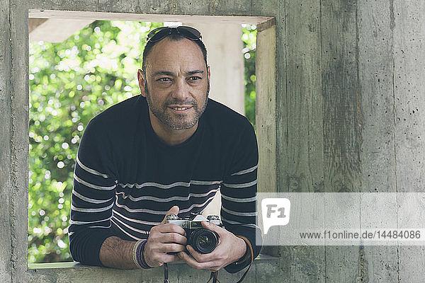 Portrait man with camera standing in garden window
