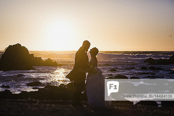 Silhouette bride and groom on tranquil sunset ocean beach  Monterey  Lucas Point  California  USA