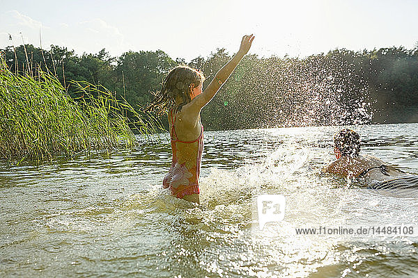 Playful girl splashing and woman swimming in sunny summer lake