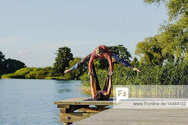 Women practicing acro yoga on sunny lakeside dock