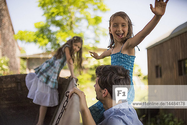 Portrait playful girl with father and sister at wagon in yard