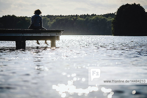 Woman relaxing at the edge of sunny lake dock