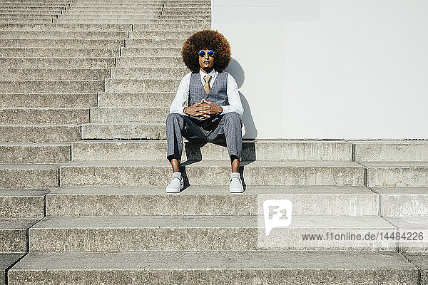 Portrait confident  cool  well-dressed young man with afro sitting on urban steps