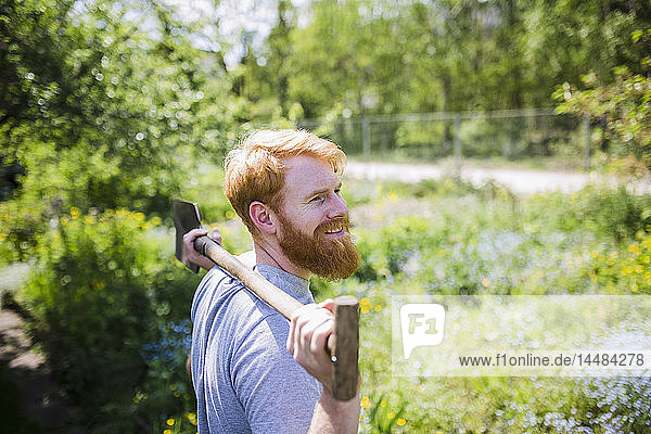 Smiling man with beard holding shovel in sunny garden