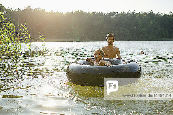 Father and daughter playing with inner tube in sunny summer lake