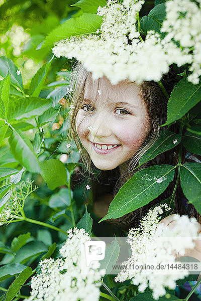 Portrait smiling girl hiding in blooming bush