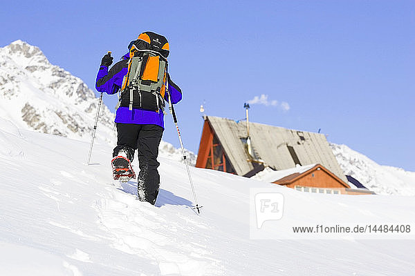 Woman Snowshoeing toward a lodge at Hatcher Pass near the Matanuska Valley. Winter in Southcentral Alaska.
