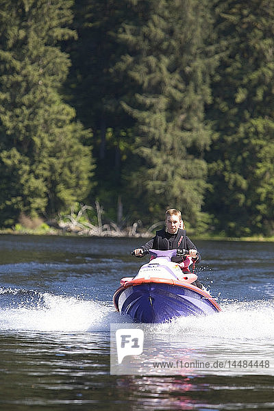 14 year old boy driving a jetski at Auke Lake north of Juneau southeast Alaska summer